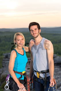 Rock climbing active couple on top sunset