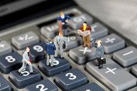 Miniature men shake hands on a calculator