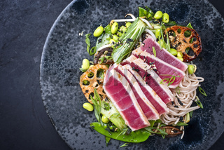 Modern style traditional Japanese gourmet seared tuna fish steak tataki with soba noodles and stir-fried vegetables served as top view on a Nordic design plate with copy space left