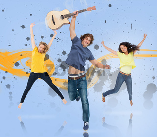 Young man with guitar and two girls jumping for joy