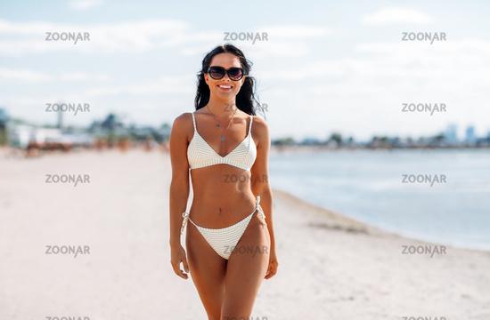 smiling young woman in bikini swimsuit on beach