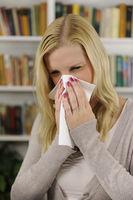 Frau putzt sich die Nase