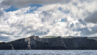 Tall Kerry Cliffs with dramatic sky, seen from a boat on Atlantic Ocean