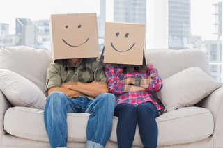 Funny workers with arms crossed wearing boxes on their heads