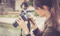 Young female tourist girl is taking shots with her camera