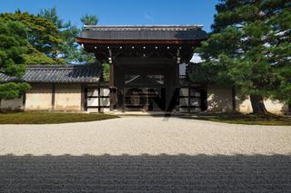 Stone zen garden with raked gravel an gate at Sogenchi garden at Tenryu-ji temple in Kyoto, Japan