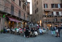 People relaxing at the coffee shops in the streets of Siena historic town Italy, Europe