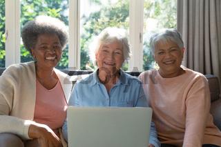Three happy diverse senior woman sitting on sofa and using laptop