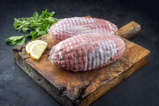 Traditional raw veal roll roast with herbs and lemon slice offered as close-up on an old rustic wooden board