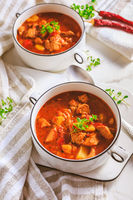 Beef goulash soup - hearty Hungarian soup of meat and vegetables seasoned with paprika on white background