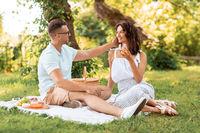 happy couple having picnic at summer park