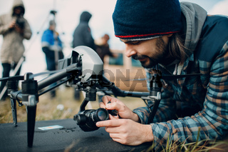 Man pilot checking quadcopter drone before aerial flight and filming.