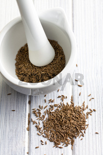 cumin seeds and ceramic mortar