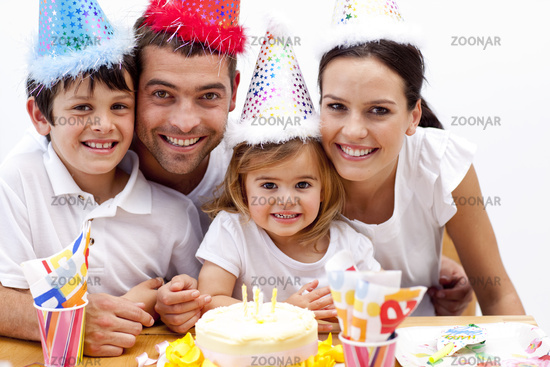 Family celebrating daughter's birthday at home