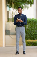 African businessman outdoors at rooftop garden using mobile phone full length shot