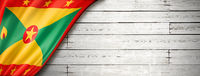 Grenada flag on old white wall banner