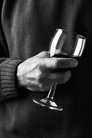 Closeup of a man holding a wine glass in front of his body. Person is unrecognizable.