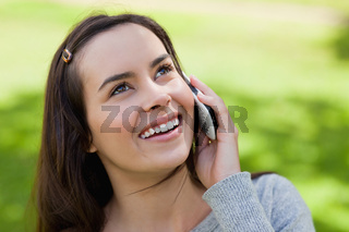 Young smiling woman talking on the phone while looking up