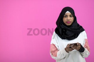 afro woman uses a cell phone in front of a pink background