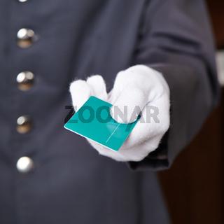 Hand eines Portiers überreicht Karte