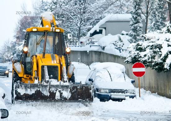 Yellow Bulldozer Snow Plowing Street In Urban Area