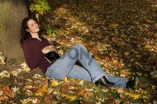 Frau entspannt im Herbstlaub
