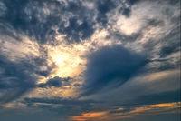 Dark cloudy sky at sunset in sunshine - abstract background