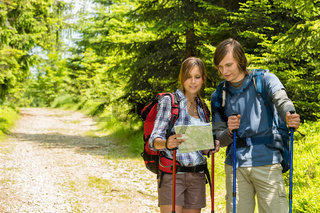 Young trekking couple checking the map