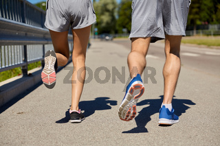 feet of sporty couple running along city road
