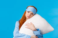 Sad redhead girl feeling depressed dont want college, lying in bed, hugging pillow, frowning and looking uneasy with concerned, nervous expression, wearing sleep mask and nightwear, blue background