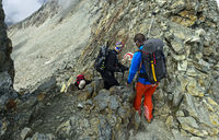 Alpinists in a narrow rock passage at the Tracuit Pass, Val d'Anniviers, Valais, Switzerland