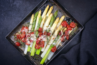 Traditional backed white and green asparagus with tomatoes and parmesan served as top view on a rustic metal tray with copy space