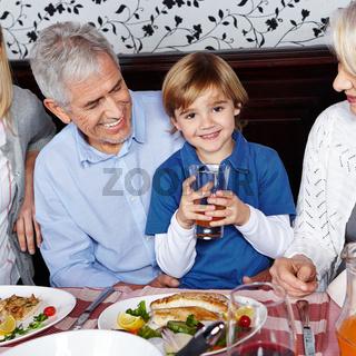 Kind trinkt Saft bei den Großeltern