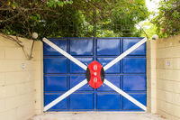 Iron gate with a white cross and a shield in a village near the town of Gede in Kenya