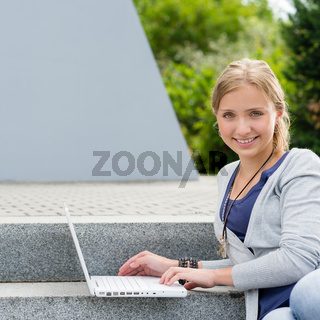 Student girl sitting on steps with laptop