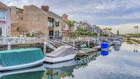 Pano Boats on docks of canal along seaside houses in Huntington Beach Califonia