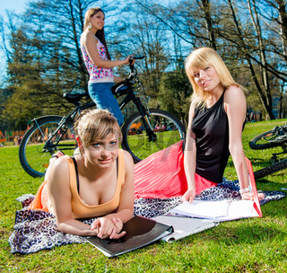 Three attractive female students relaxing outdoors