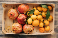 A wooden box with tangerines, lemons and pomegranates. Fruits collected in the autumn garden.