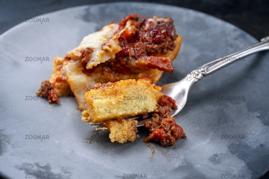 Modern style traditional Italian polenta alla sarda con salsiccia with ground meat ragu and pecorino served as top view on a ceramic design plate