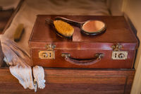 Vintage leather travel suitcase on wooden bed with brush and mirror on the top