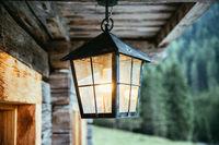 Lantern is hanging in on the veranda of an olden wooden hut
