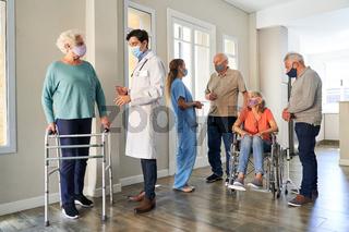 Gruppe Senioren und Arzt mit Mundschutz wegen Covid-19