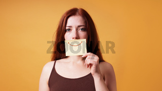 young woman hiding emotion with fake smile drawn on paper