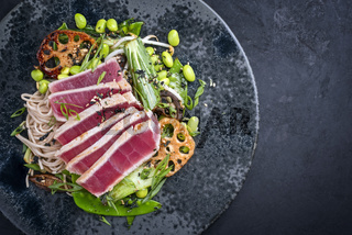 Modern style traditional Japanese gourmet seared tuna fish steak tataki with soba noodles and stir-fried vegetables served as top view on a Nordic design plate with copy space right
