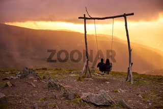 Romantic couple social distancing swinging on a Swing baloico in Lousa mountain, Portugal at sunset