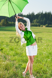 Happy young woman with green umbrella meadows