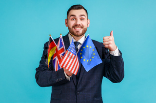 Portrait of happy bearded businessman wearing official style suit holding flags of Germany, USA, Great Britain and Europe Union, showing thumb up.