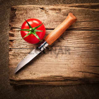 Fresh organic ripe tomato and steel knife