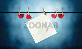 Blank paper cards hanging on clothespins  together with red hearth shapes