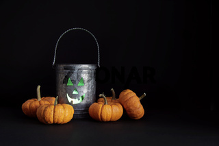 Metal tin with candle and gourds on black